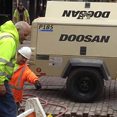 Picture showing a Doosan Compressor being used in high street maintenance