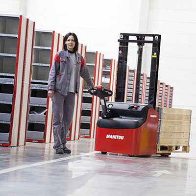 Picture showing a woman operating a Manitou warehouse truck